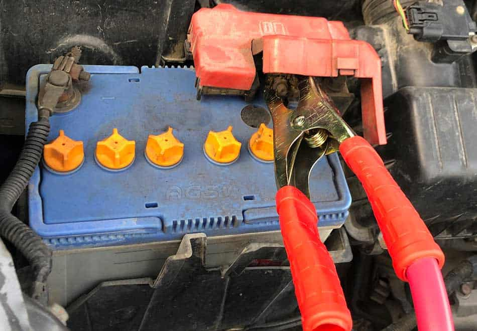 red jumper cable connected to jumper car's battery
